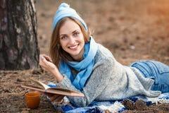 A menina loura bonita que descansa na floresta da mola ou do outono leu o livro e, encontre-se com o copo do chá e do livro Cauca Imagens de Stock Royalty Free