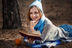 A menina loura bonita que descansa na floresta da mola ou do outono leu o livro e, encontre-se com o copo do chá e do livro Cauca Imagem de Stock