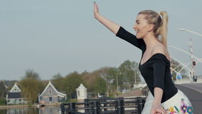Menina loura bonita que está na ponte e que acena a alguém filme