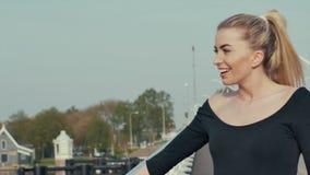 Menina loura bonita que está na ponte e que aprecia a vista vídeos de arquivo
