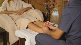 Menina loura bonita que faz a massagem do pé Massagem terapêutica filme