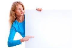 Menina loura bonita que guarda uma placa branca vazia Fotos de Stock