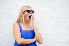 Menina loura bonita que olha o filme assustador com vidros 3D, excitação escondendo guardando as mãos Close up do retrato Imagens de Stock
