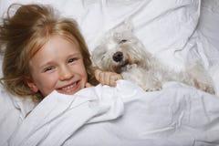 Menina loura bonita que ri e que encontra-se com o cão de cachorrinho branco do schnauzer na cama branca Conceito da amizade Imagem de Stock Royalty Free