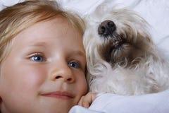 Menina loura bonita que ri e que encontra-se com o cão de cachorrinho branco do schnauzer na cama branca Conceito da amizade Foto de Stock Royalty Free