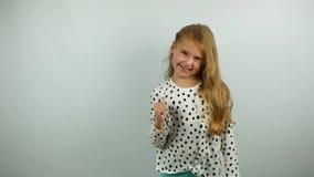 Menina loura bonita que sorri e que gesticula Movimento lento do gesto do yes pela criança bonito filme