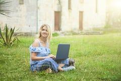 Menina loura bonita que trabalha em um portátil no parque foto de stock
