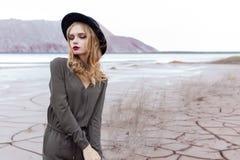 Menina loura bonita, 'sexy' que levanta nas montanhas em uma terra rachada em um chapéu negro com composição brilhante Foto de Stock