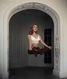 A menina loura bonita voa na posição de lótus no interior branco com arco mágica da levitação Mulher que faz a ioga fotografia de stock