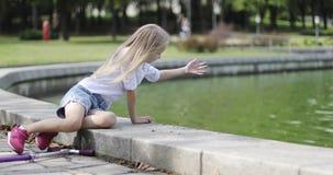Menina loura bonito com o cabelo longo que senta-se perto do lago no parque vídeos de arquivo