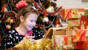 A menina loura bonito, com uma curva cor-de-rosa em seu cabelo, em um vestido bonito está olhando algo em uma tabuleta, perto dos vídeos de arquivo