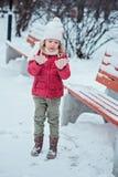 Menina loura bonito da criança que olha suas mãos na caminhada no parque nevado do inverno Imagem de Stock Royalty Free