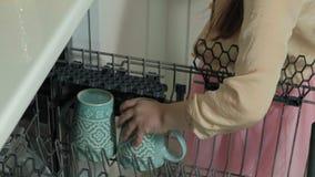 A menina loura bonito do borracho em uma saia cor-de-rosa, ajuda a mamã na cozinha brilhante, apresenta as placas, copos da máqui filme