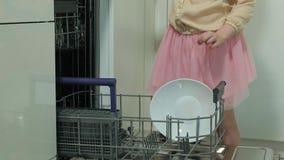 A menina loura bonito do borracho em uma saia cor-de-rosa, ajuda a mamã na cozinha brilhante, placas das cargas, copos na máquina filme