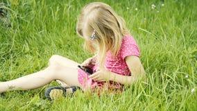 Menina loura bonito na idade pré-escolar que senta-se na grama verde que joga com telefone esperto filme