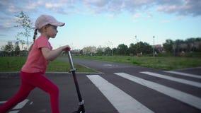 Menina loura bonito pequena no parque cor-de-rosa do 'trotinette' dos passeios do tampão em público video estoque