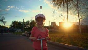 Menina loura bonito pequena no parque cor-de-rosa do 'trotinette' dos passeios do tampão em público vídeos de arquivo