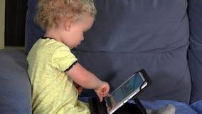 Menina loura bonito que joga o jogo l?gico com tablet pc em casa vídeos de arquivo