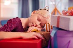 Menina loura cansado do aniversário que dorme em presentes imagens de stock