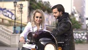 Menina loura caucasiano atrativa na camisa branca no regulador de pressão do aperto de torção da motocicleta, homem do motociclis filme