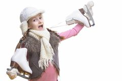 Menina loura caucasiano de sorriso engra?ada na roupa do inverno Levantamento com os patins de gelo sobre o ombro nas m?os na par fotografia de stock