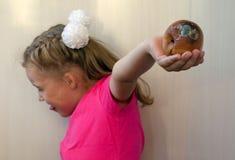 A menina loura com aversão abandona a pera podre imagem de stock royalty free