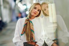 A menina loura com a cidade urbana defocused ilumina-se na noite imagem de stock royalty free