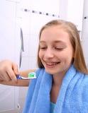 Menina loura com cintas que sorri ao escovar seus dentes fotografia de stock