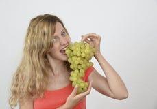 Menina loura com grupo de uvas isoladas no branco Fotografia de Stock Royalty Free