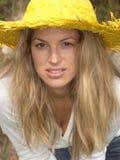 Menina loura com o chapéu amarelo que inclina-se para a frente imagens de stock