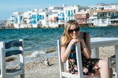 Menina loura com os óculos de sol que sentam-se em uma cadeira na praia Fotos de Stock
