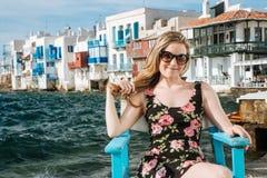 Menina loura com os óculos de sol que sentam-se em uma cadeira na praia Imagens de Stock