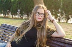Menina loura com os vidros que sentam-se em um banco no parque contra a luz fotografia de stock
