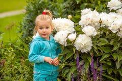 Menina loura com peônias brancas Imagem de Stock