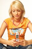 Menina loura com telefone de pilha Fotografia de Stock