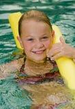 Menina loura com um macarronete do styrofoam Fotos de Stock Royalty Free
