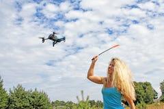 A menina loura com uma mata-moscas de mosca conduz afastado o zangão fotos de stock royalty free