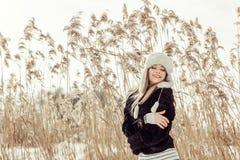 A menina loura consideravelmente atrativa dos jovens com cabelo do blondie na estação do inverno tem uma boa estadia exterior Foto de Stock Royalty Free