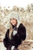 A menina loura consideravelmente atrativa dos jovens com cabelo do blondie na estação do inverno tem uma boa estadia exterior Fotografia de Stock Royalty Free