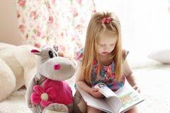 A menina loura consideravelmente pequena senta-se perto do brinquedo macio no tapete e lê-se Fotografia de Stock