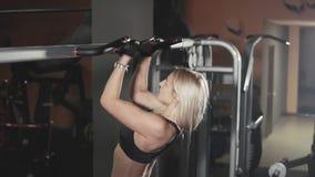 A menina loura da aptidão com o cabelo longo que faz a tração levanta no gym escuro no movimento lento filme
