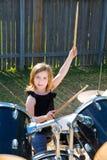 Menina loura da criança do baterista que joga cilindros no quintal do tha imagens de stock royalty free