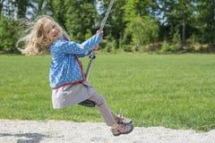 A menina loura da criança feliz (idade 5) livra no equipamento do jogo do Fox de voo em um campo de jogos das crianças imagens de stock royalty free