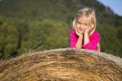 Menina loura da criança pelo pacote de feno da palha no campo Fotografia de Stock