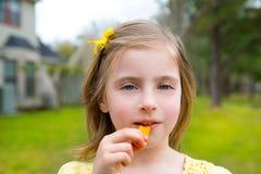 Menina loura da criança que come petiscos do milho no parque exterior Foto de Stock Royalty Free