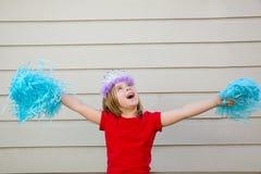 Menina loura da criança que joga como poms e a coroa cheerleading do pom Fotografia de Stock