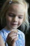 Menina loura da criança que mostra e que estuda o caracol novo pequeno Imagem de Stock