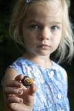 Menina loura da criança que mostra e que estuda o caracol novo pequeno Imagens de Stock Royalty Free