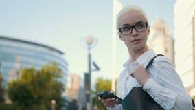 Menina loura da mulher de negócios nova bonita nos vidros que chama pelo telefone no centro de negócios do fundo Imagem de Stock Royalty Free