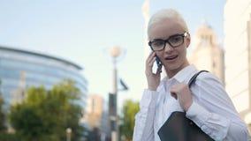 Menina loura da mulher de negócios nova bonita nos vidros que chama pelo telefone no centro de negócios do fundo Imagens de Stock